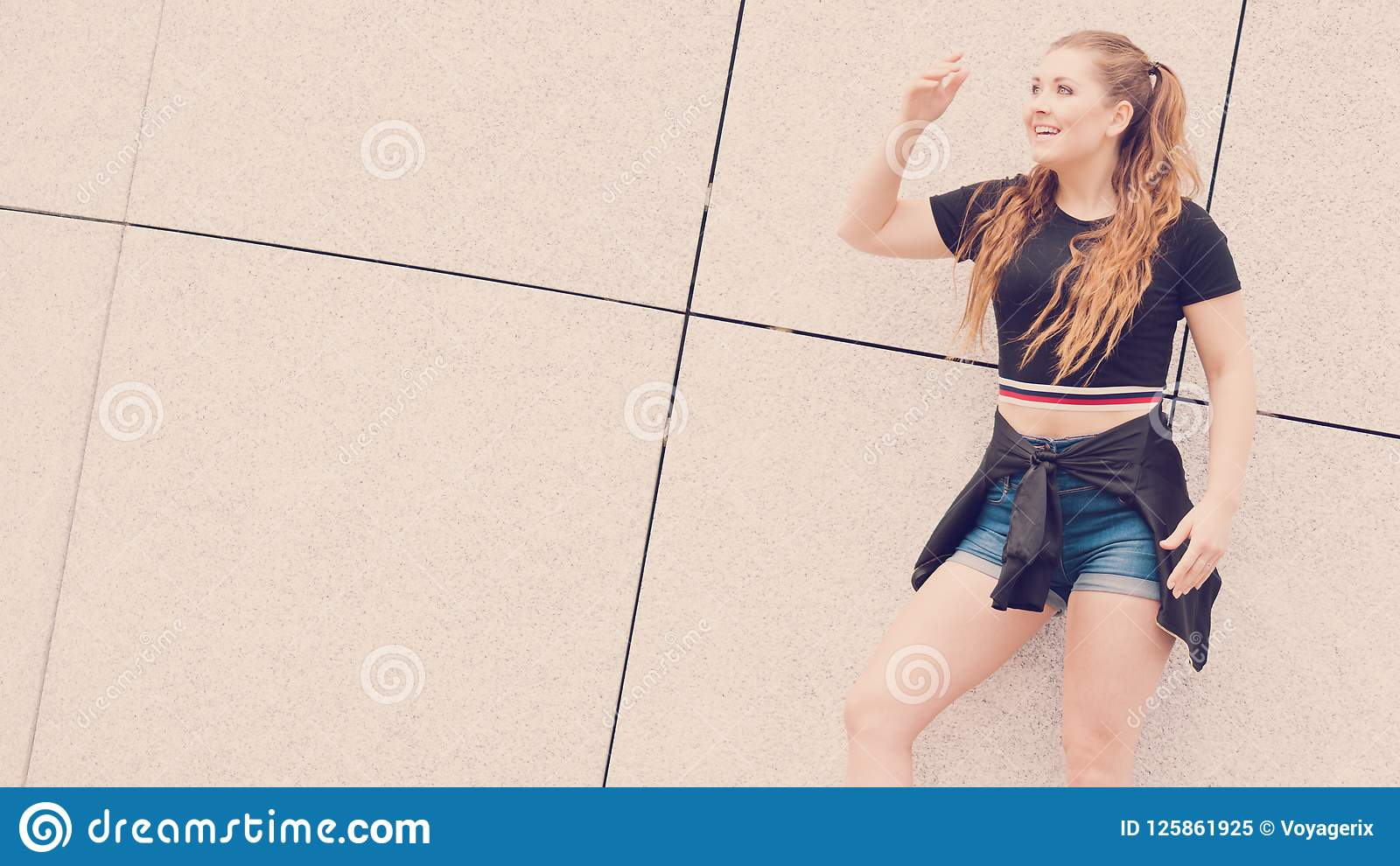 cdd3ad28e7c7 Young teenage woman wearing denim shorts and black crop top. Female  presenting fashionable summer outfit.