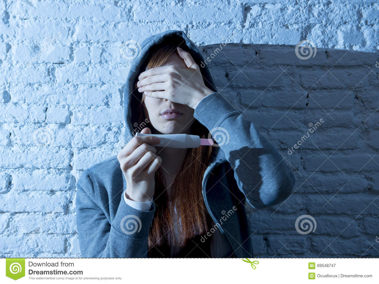 Young teenager girl or young woman in shock scared after positive pregnancy test