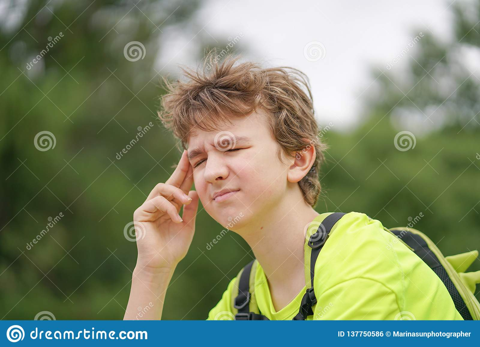 A young teenager guy is suffering from a headache. he keeps his hands to his head and winces of discomfort, sitting on the nature.