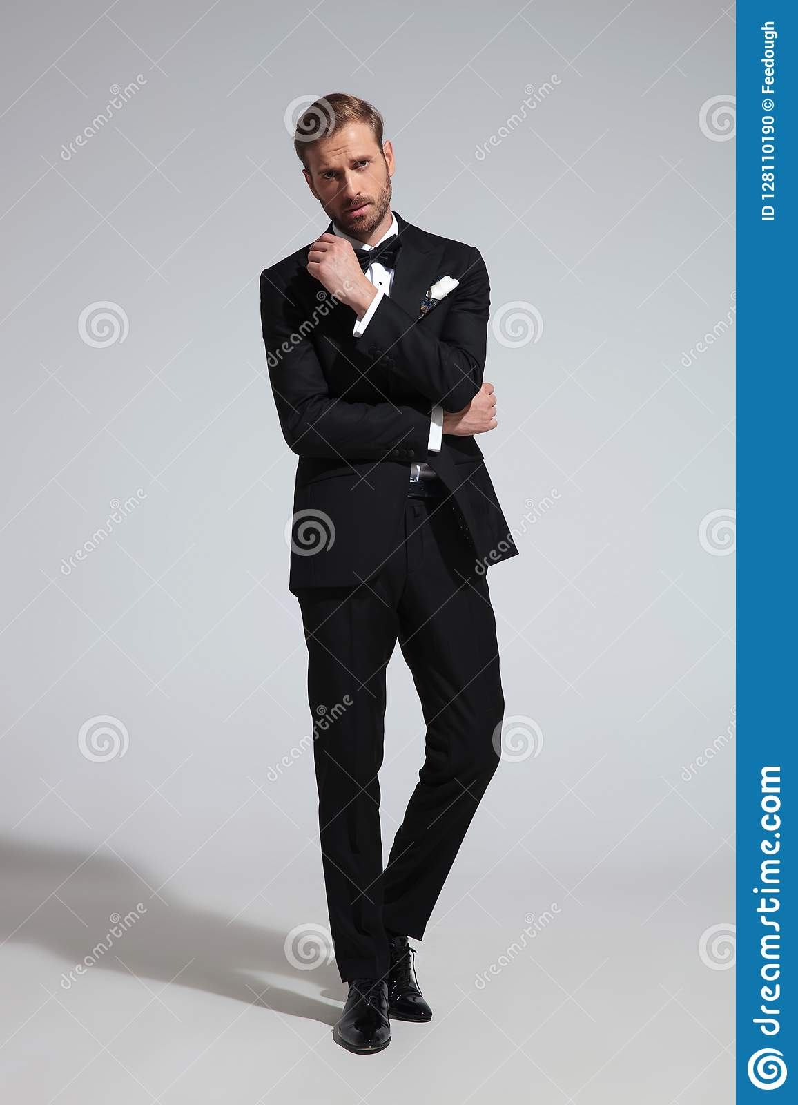 f3d0c8469f11 Young thoughtful elegant man in tuxedo and bowtie standing on gray  background