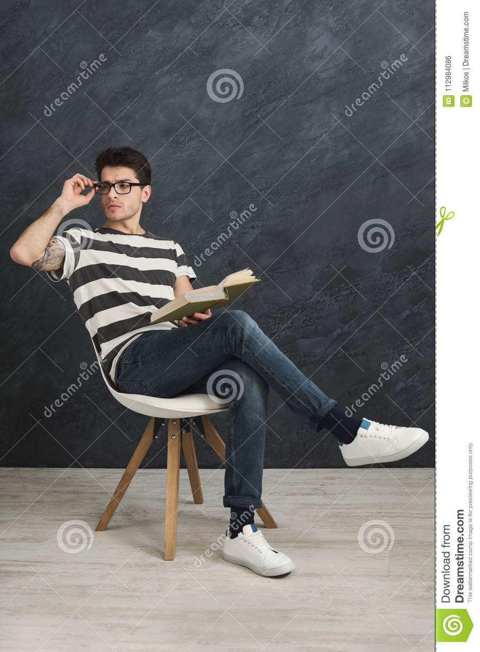 Young thoughtful tattooed man with book