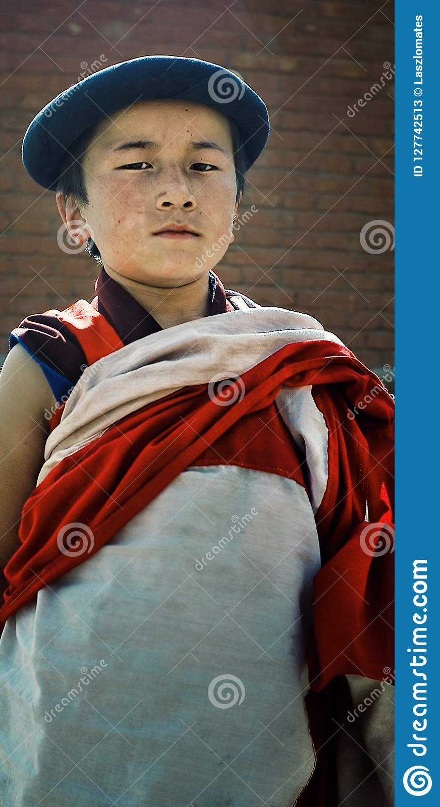 young tibetan buddhist novice monk in fromt of a brick wall with a traditional dress and hat