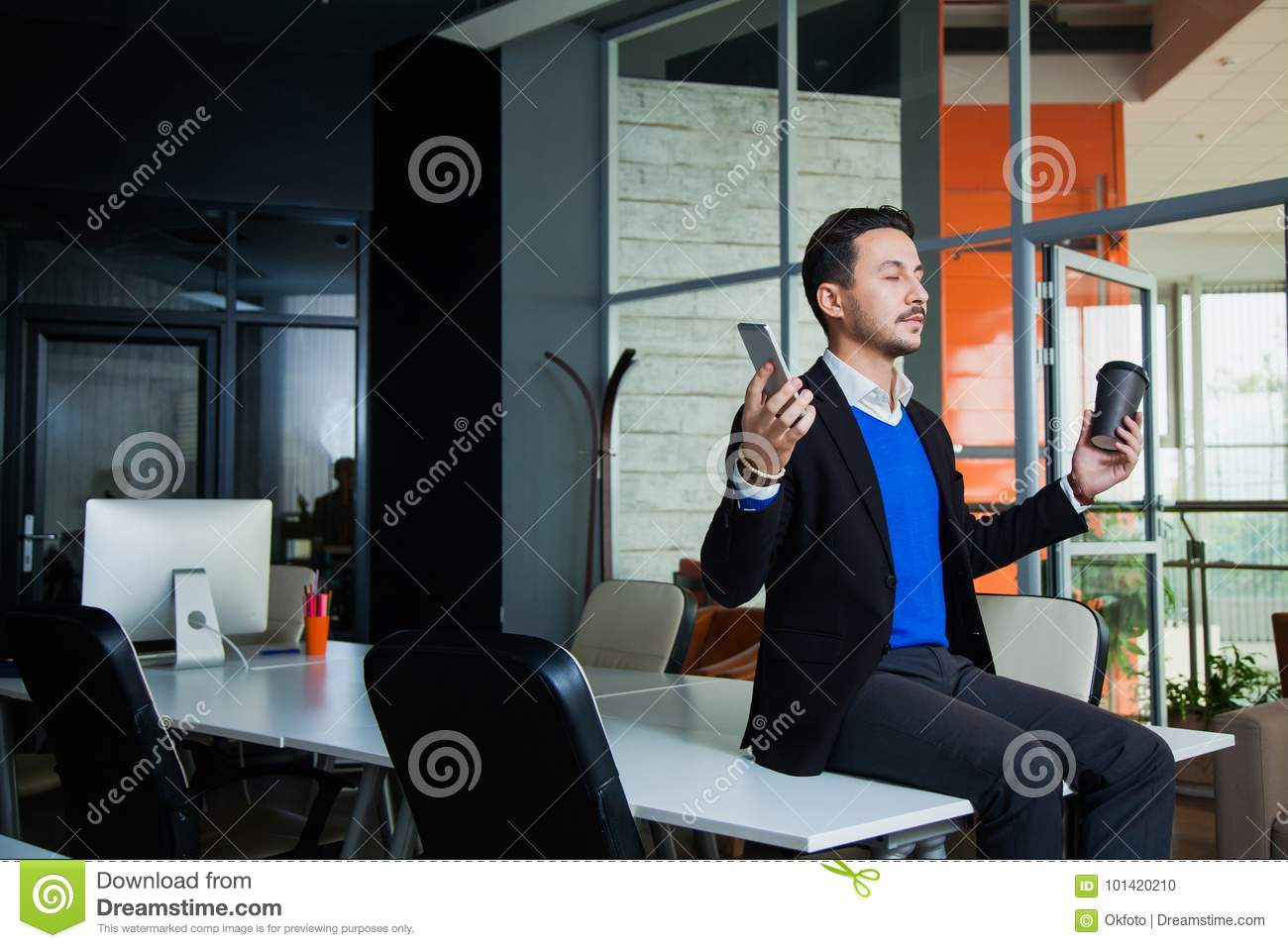 Young tired businessman meditating on table with mobile phone and coffee