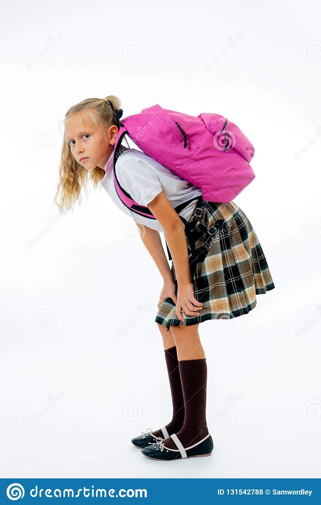 Young tired and sad cute school girl standing with a big heavy school bag on her back on a isolate white background for a back
