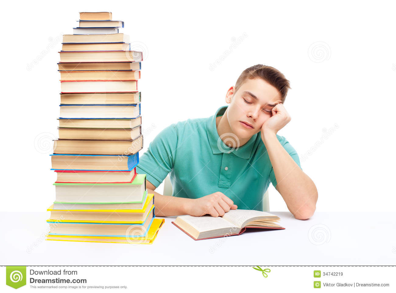 Young tired student sitting at the desk with high books stack isolated ...