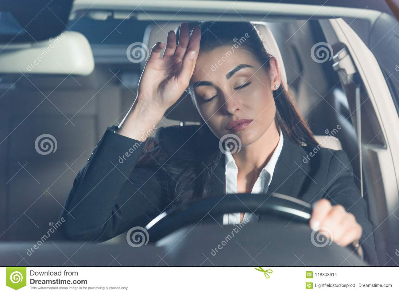 Young tired woman in suit sitting in driver seat and touching
