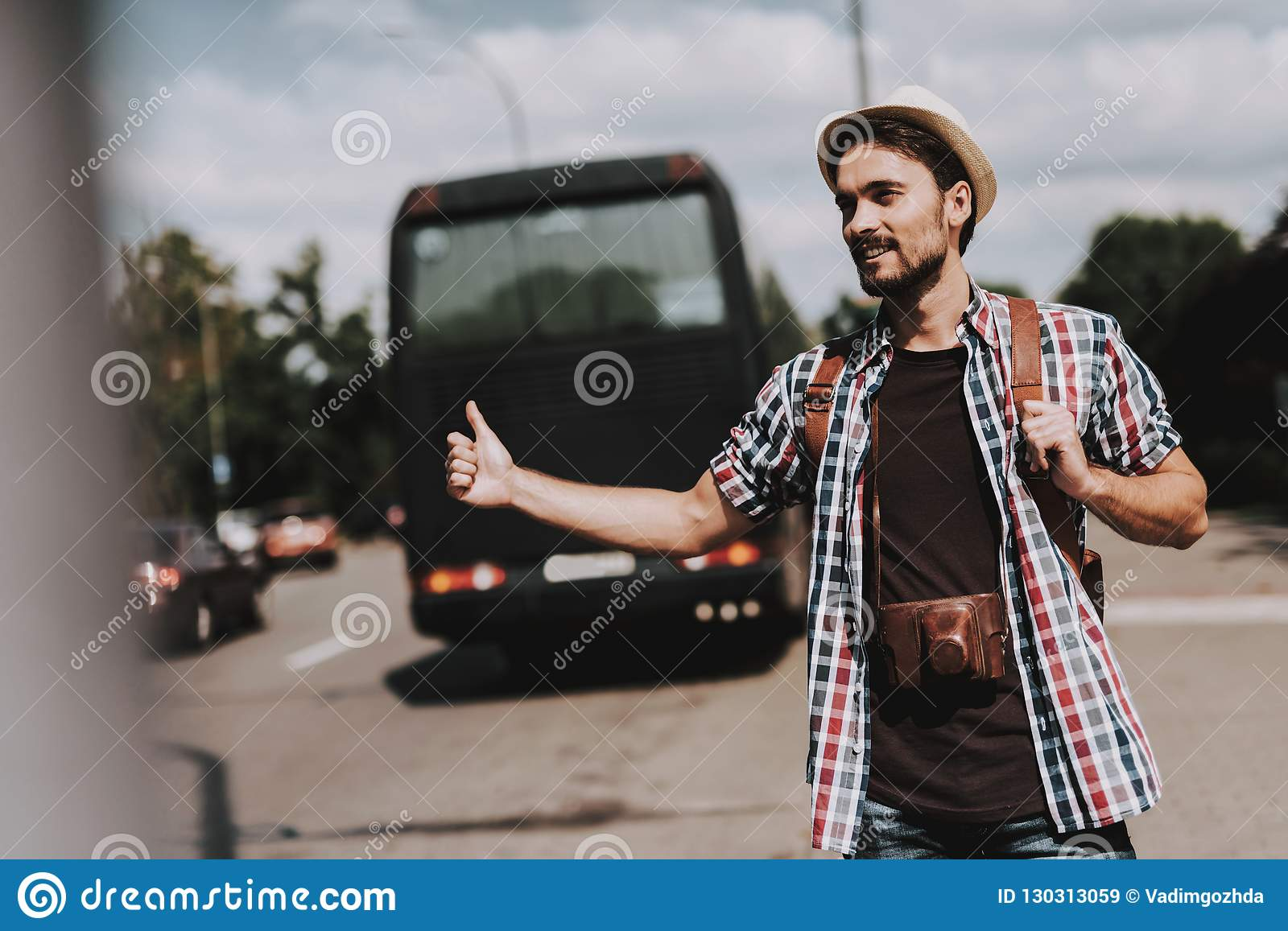 Young Tourist with Backpack Hitchhiking on Road