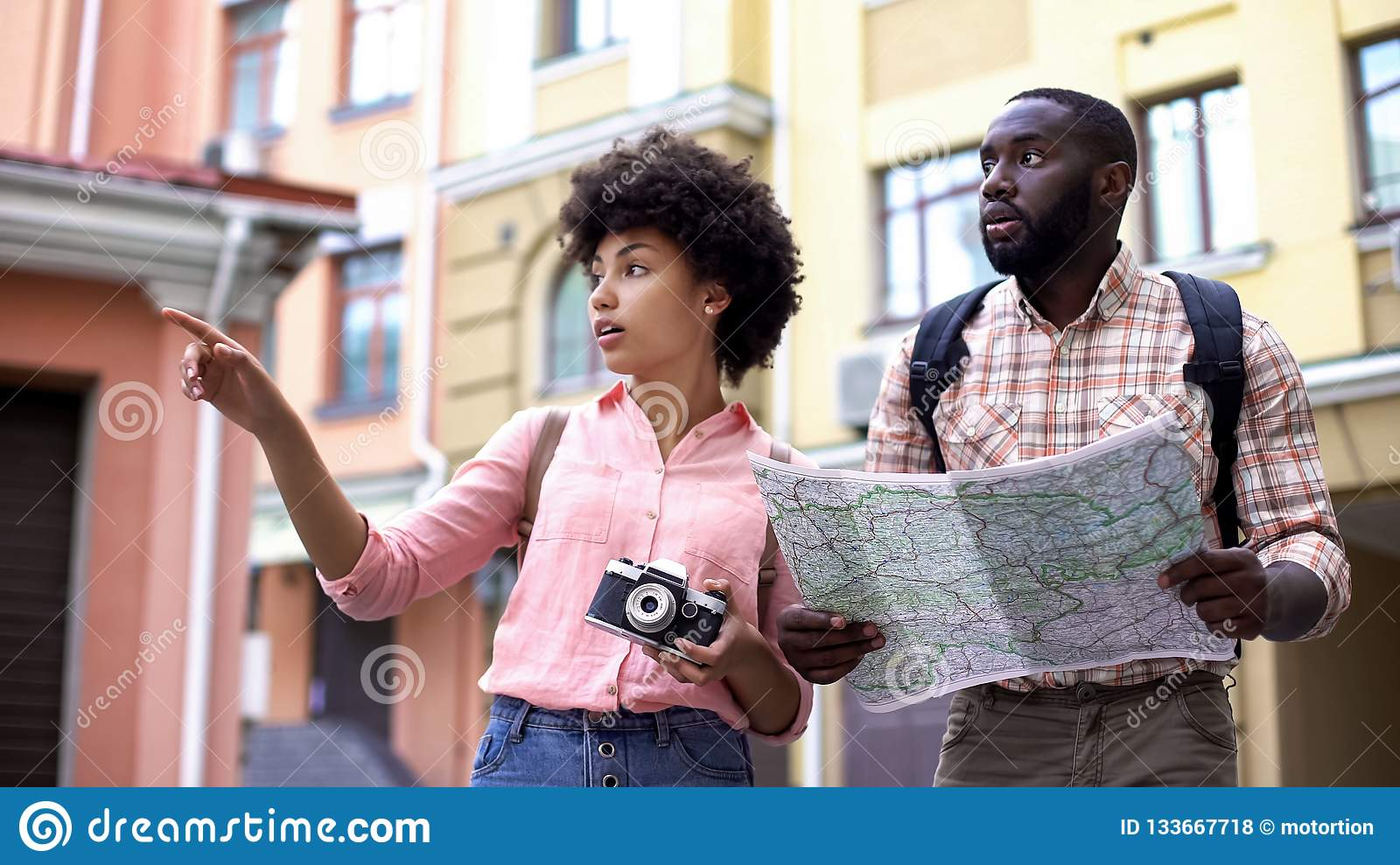 Young tourist couple with map and photo camera, choosing direction, travel