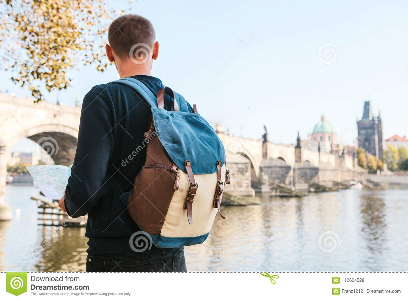 dcdbfa5abfbf A young tourist man with a backpack standing next to the river Vltava in  Prague looks