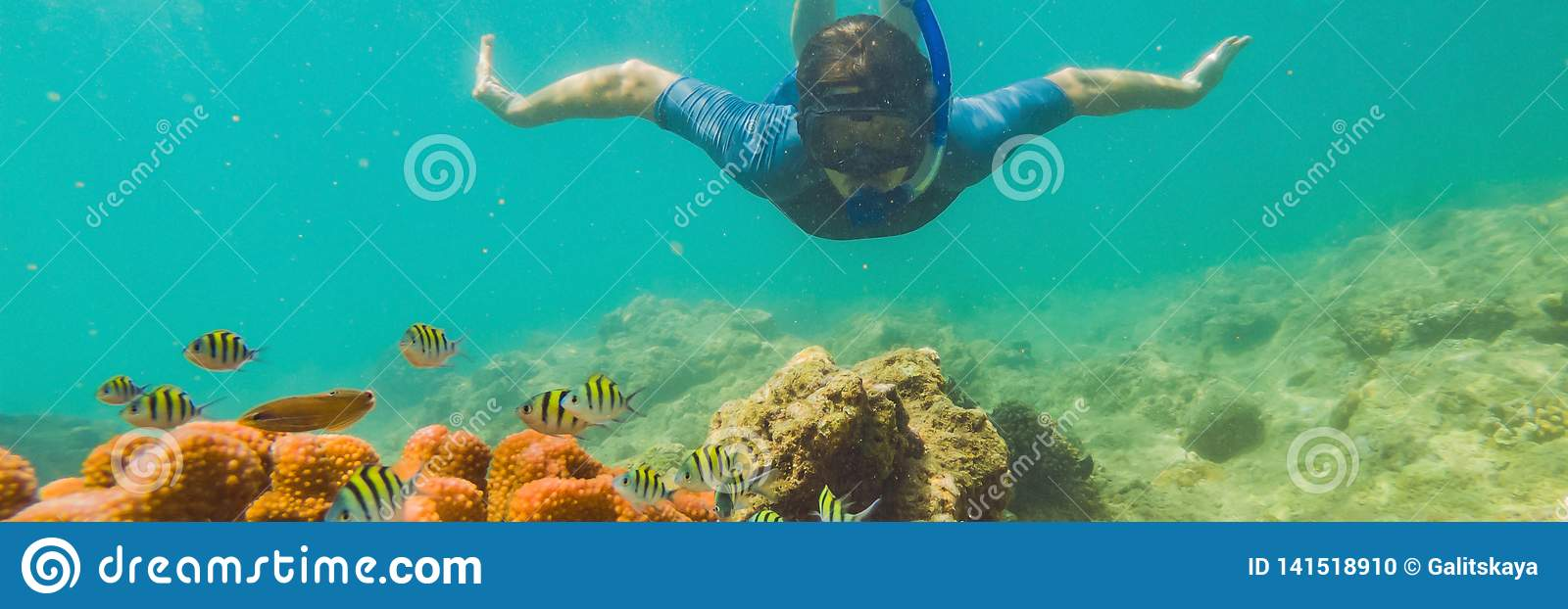 Young tourist man swimming in the turquoise sea under the surface near coral reef with snorkelling mask for summer