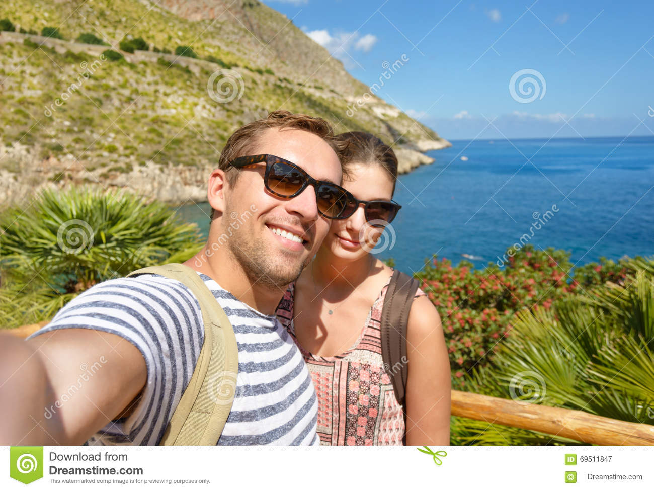 Young tourist take a selfie memory photo in tropical scenery during vacation around Italian coasts. Smiling couple.