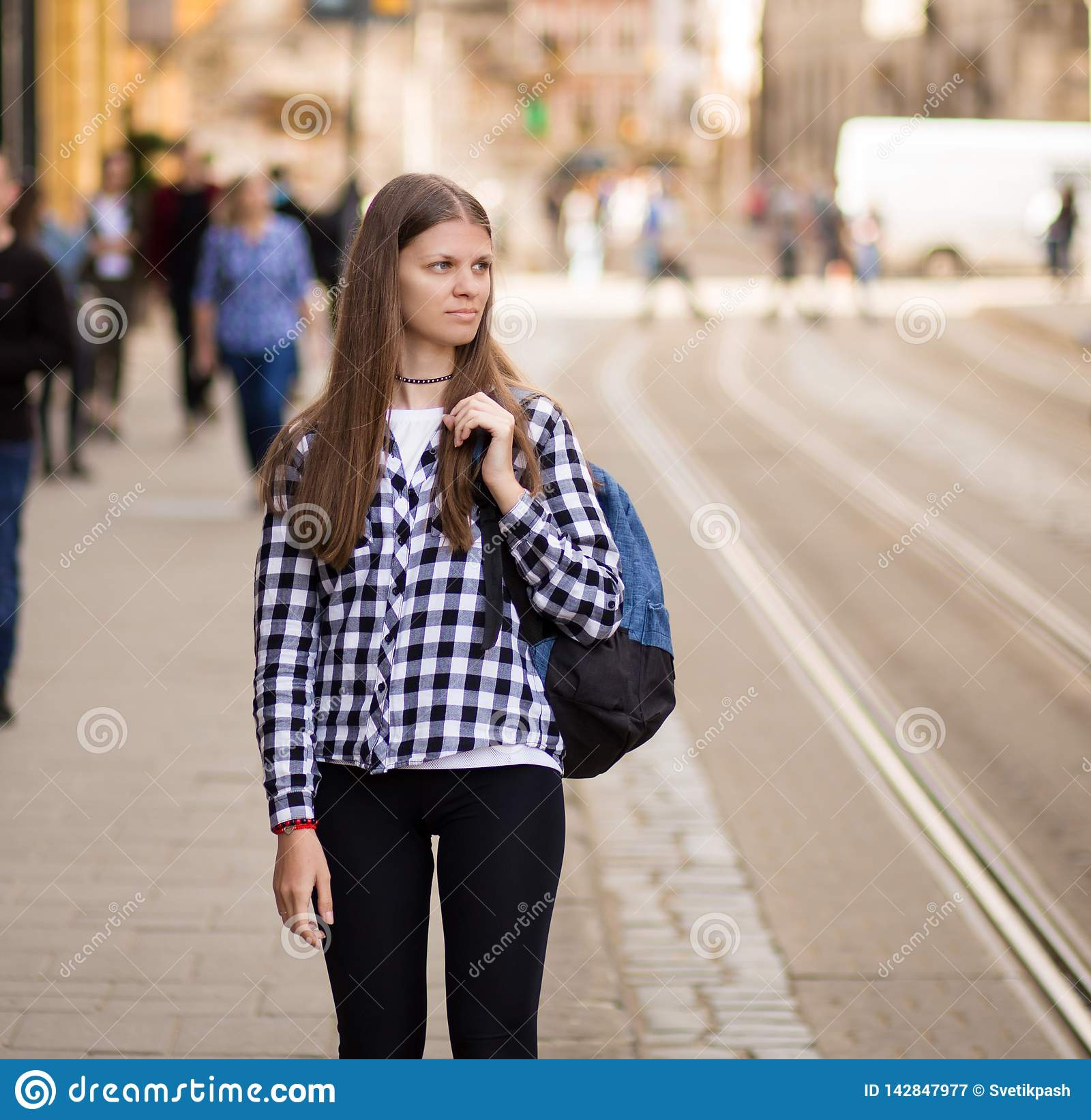Young tourist woman with backpack walk by street in old europe city, summer fashion style
