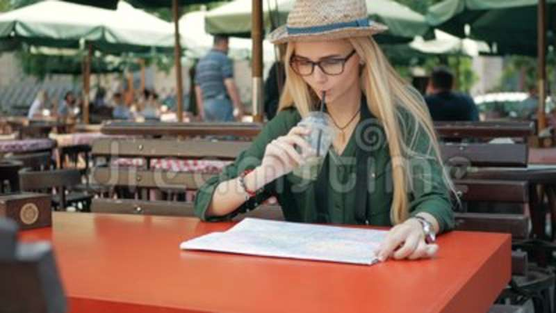 Young tourist woman exploring city map of lviv in cafe and drink while  traveling in Ukraine, vacation concept