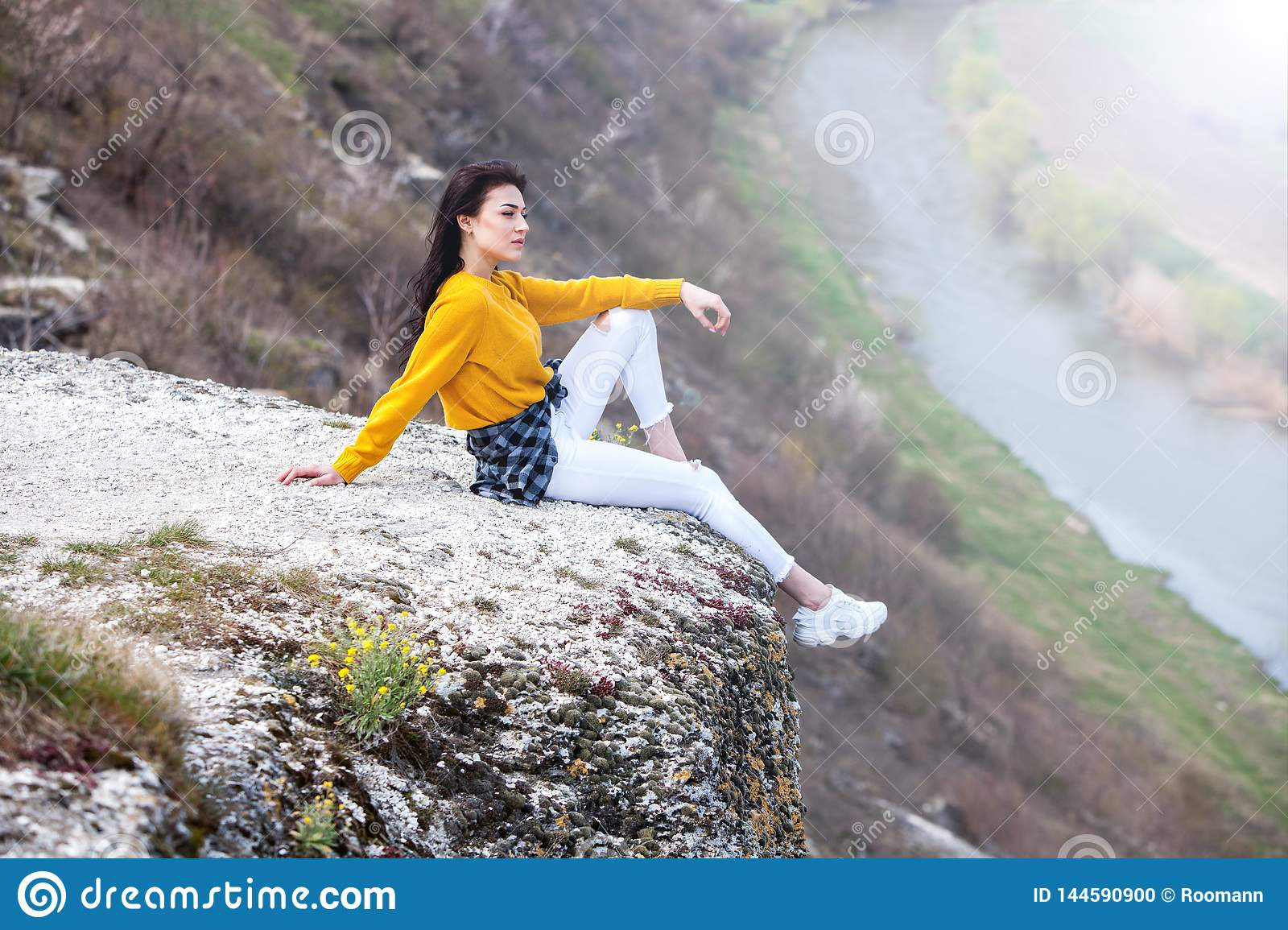 A young traveler girl sit on the top of valley. Young girl love wild life, travel, freedom. Travel Tourist Happy Woman. Travel and