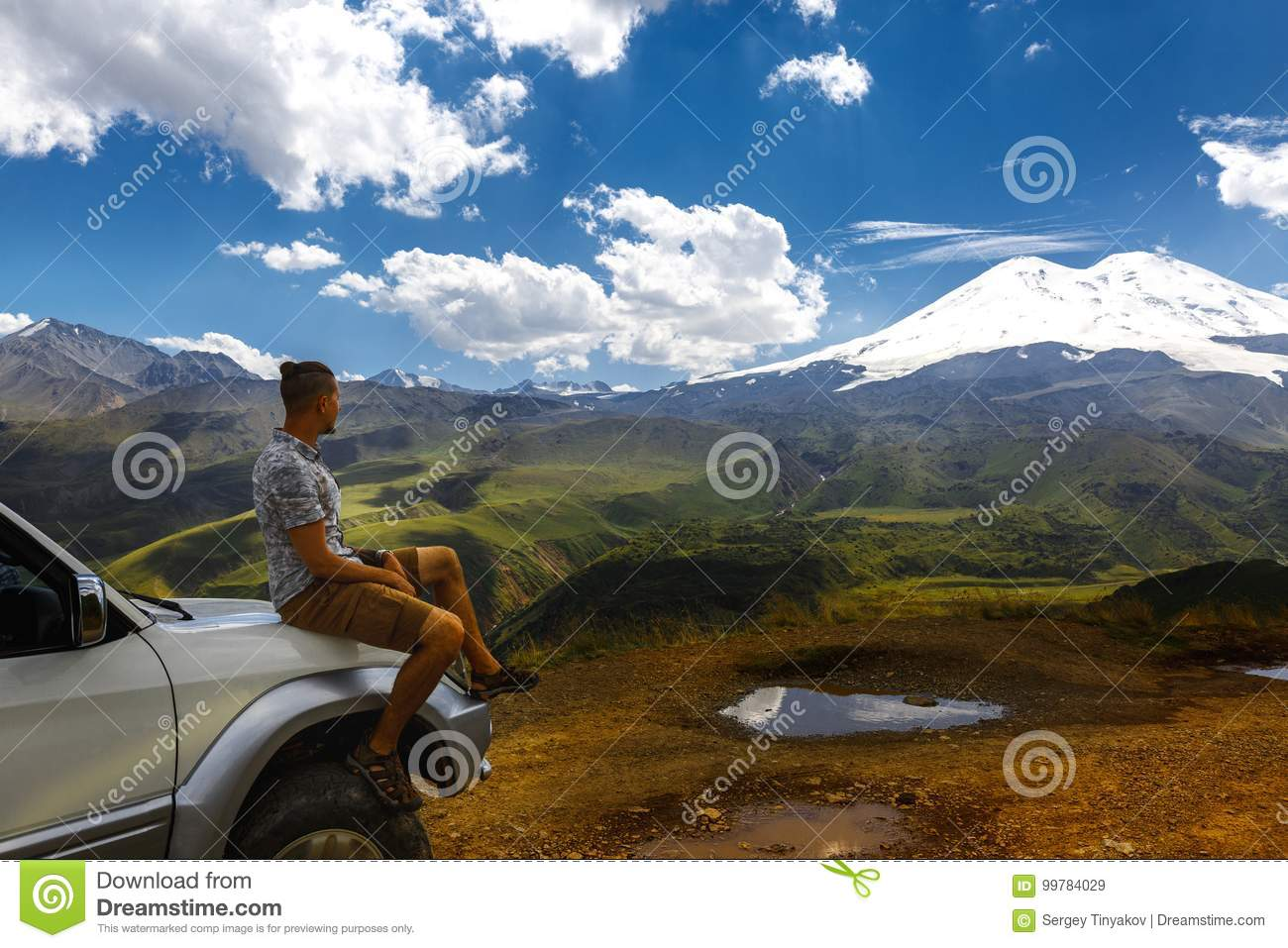 Young Traveler Man Sits On Car And Enjoys View Of Mountains In Summer. Elbrus Region, North Caucasus, Russia