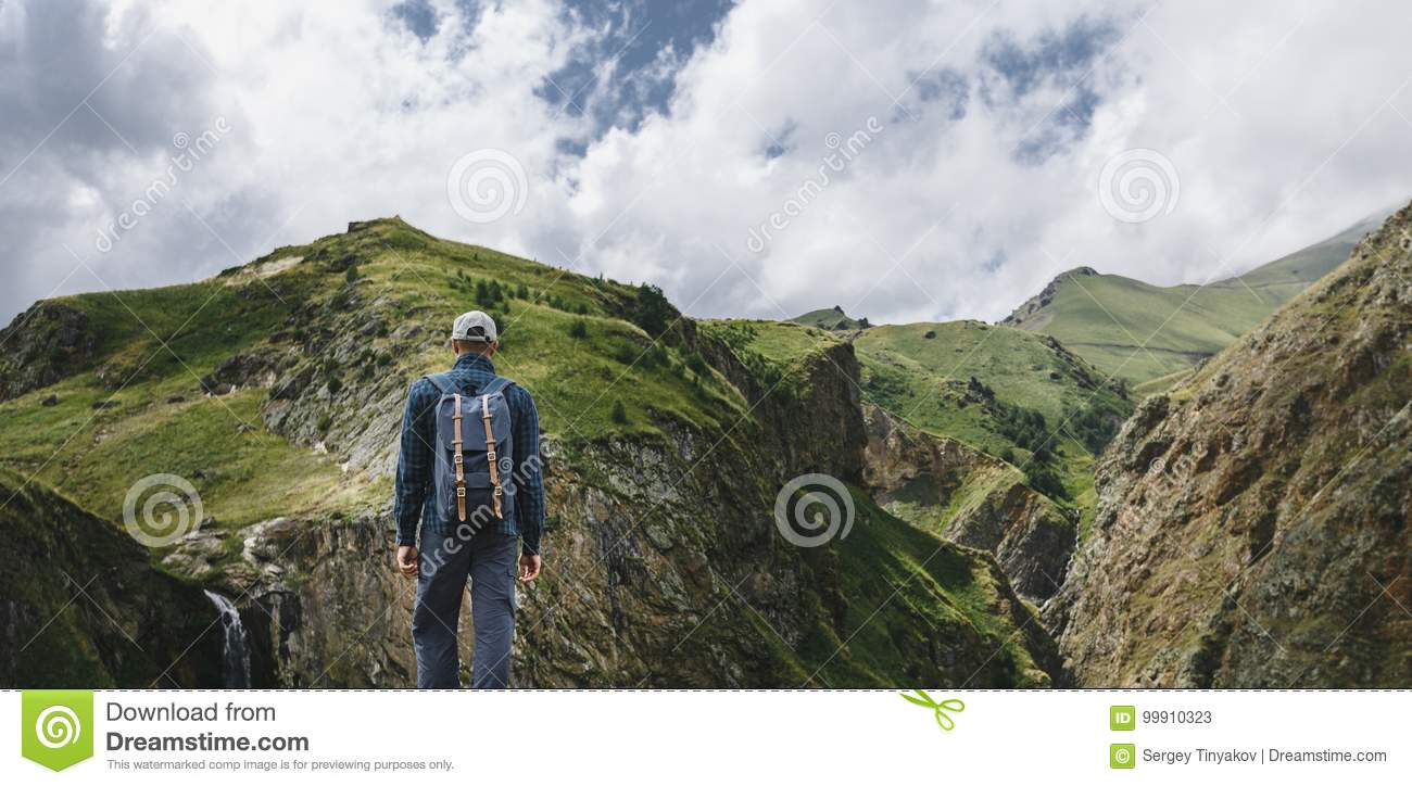 Young Traveler Man Standing On Top Of Cliff In Mountains And Enjoying View Of Nature, Rear View