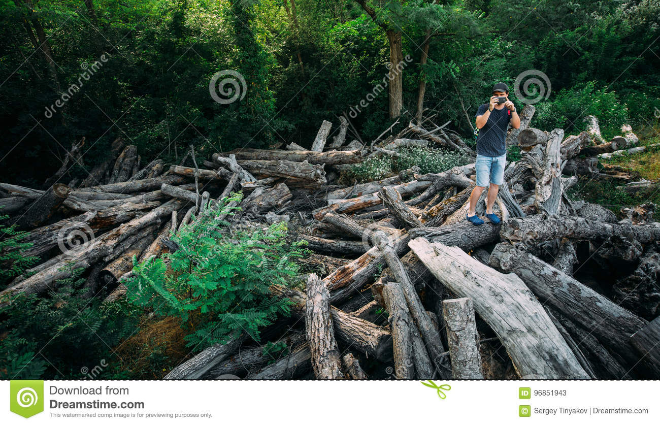 Young Traveler Man Stands On Logs And Takes Photos On Smartphone Camera With Copy-Space Left