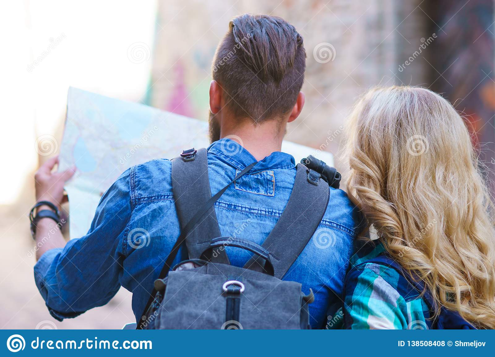 Young travelers with a tourist map. Man and woman having vacation. Backpackers, traveling and tourism concept.