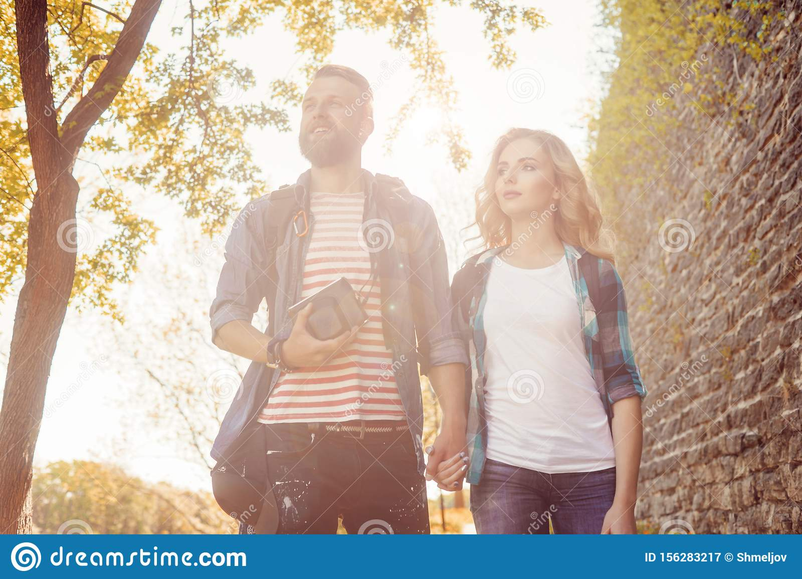 Young travelers walking in autumn park. Man and woman having vacation. Backpackers, traveling and tourism.