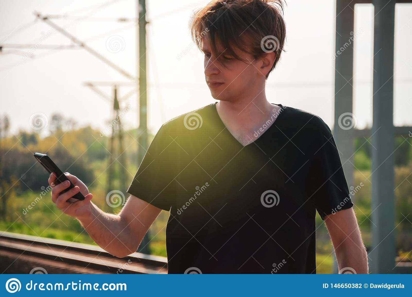 Young traveller man talking through the phone at the railway station during hot summer weather, making gestures while talking