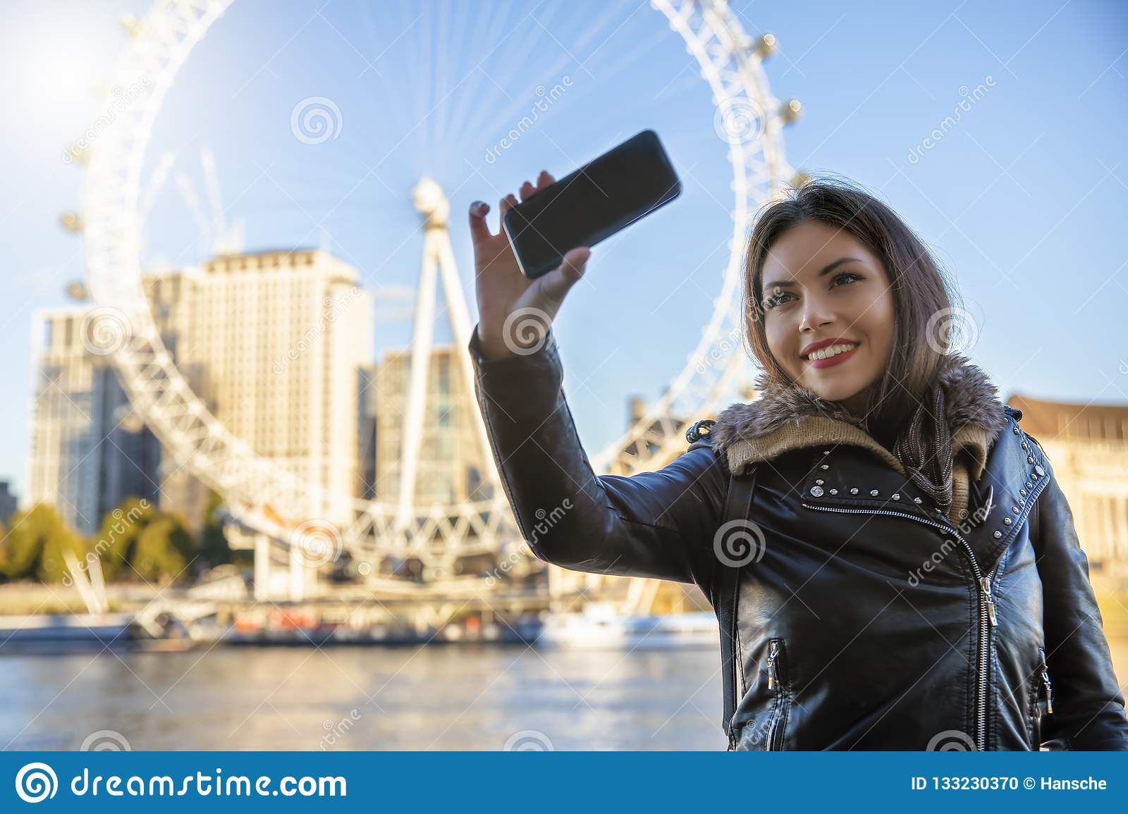 Young traveller woman talks a selfie in front of major sightseeing attractions in London, UK
