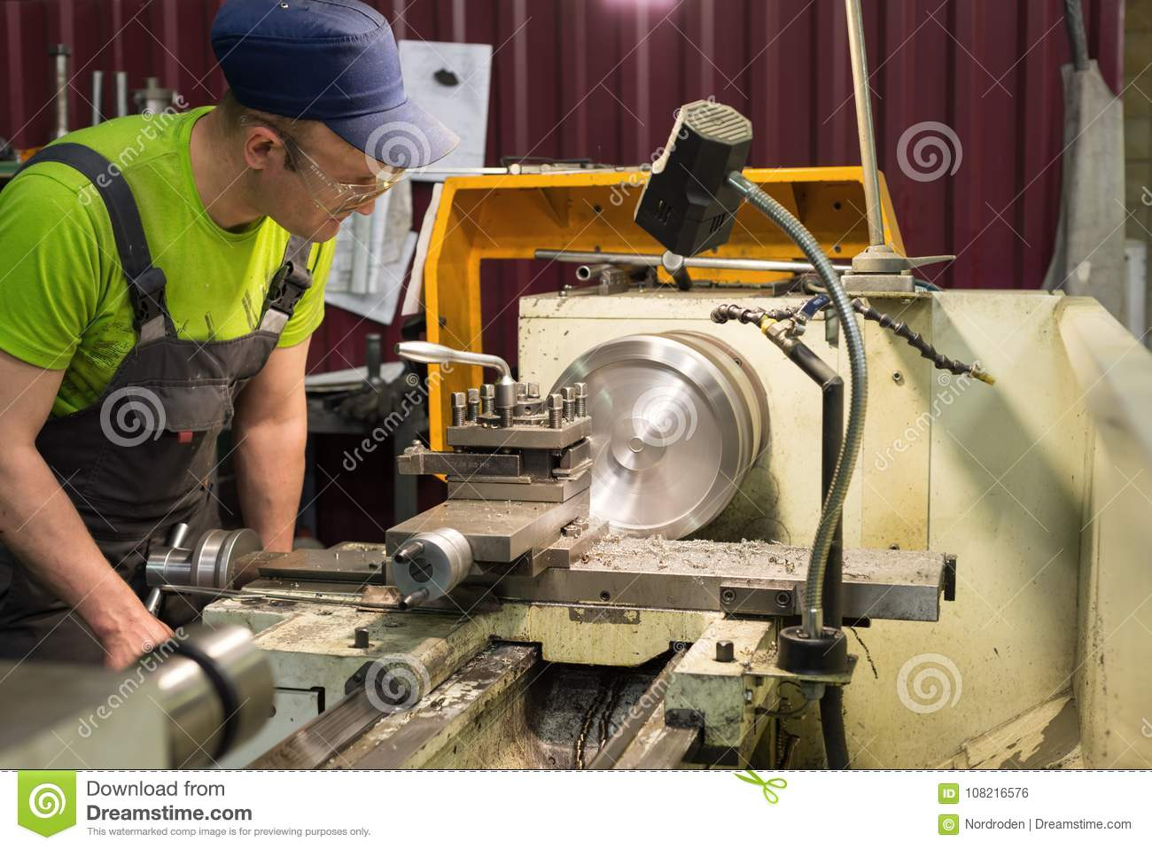 A young turner processes a metal workpiece on a mechanical lathe.