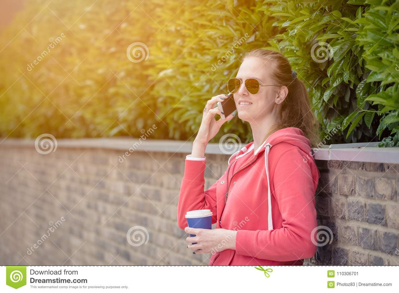 Portrait of young female making a call by using smartphone and h