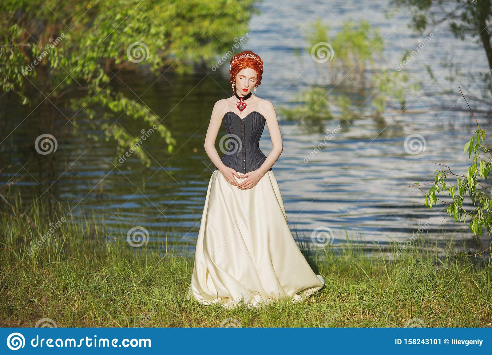 Young victorian princess with hairstyle on nature background. Rococo queen in white historic dress against backdrop of blue water