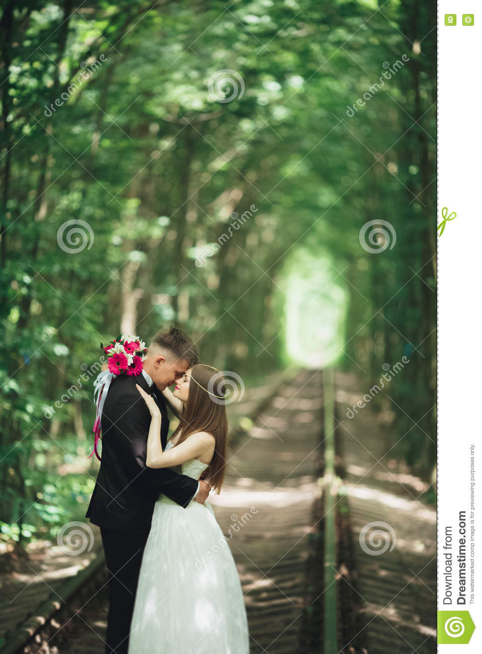 young wedding couple bride and groom posing on a railway track