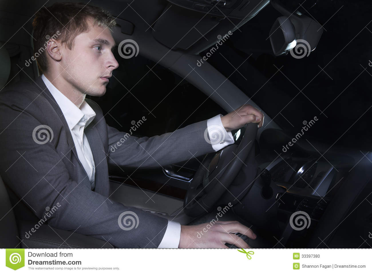 young welldressed man in a suit is sitting in his car