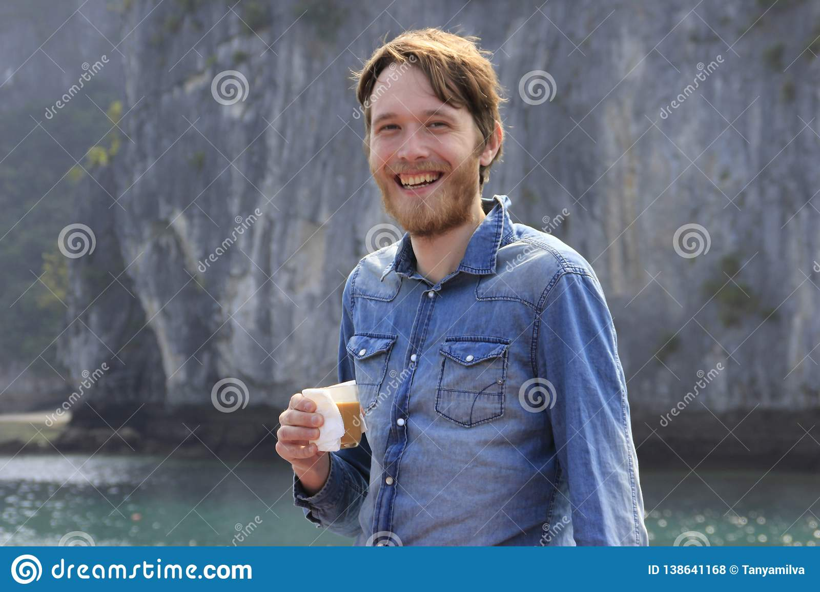 Young white attractive blond man with a beard in a blue denim shirt laughing defiantly with a glass of coffee on the background of