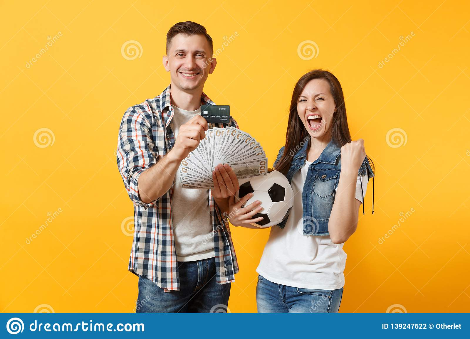 Young win couple, woman man, football fans holding bundle of dollars money, credit card, soccer ball, cheer up support