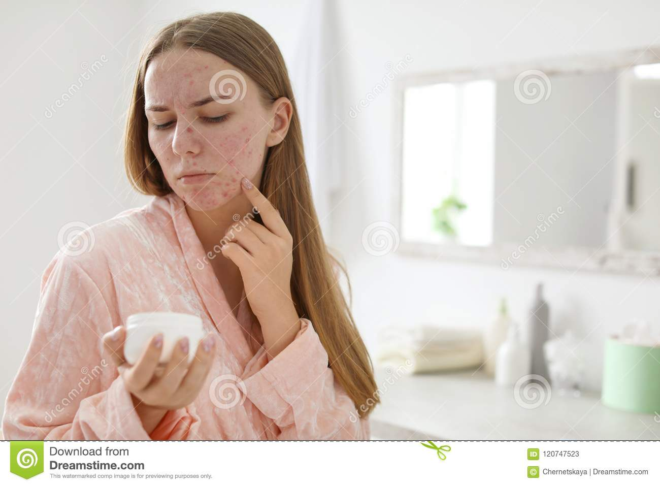 Young woman with acne problem holding jar