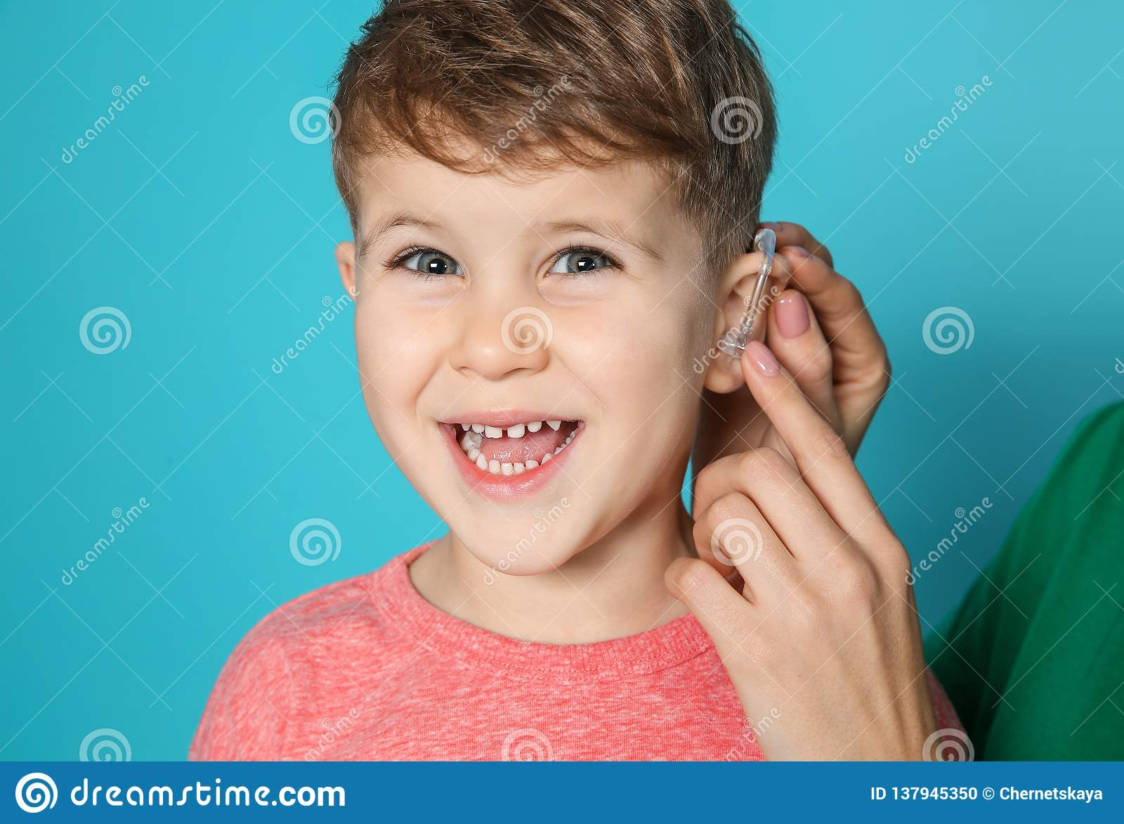 Young woman adjusting little son`s hearing aid on color background