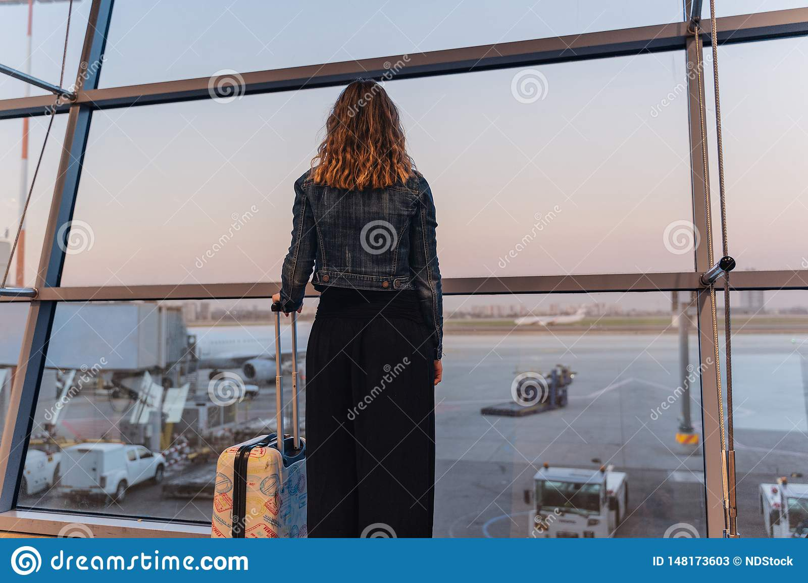 Young woman in a airport looking at the planes before departure