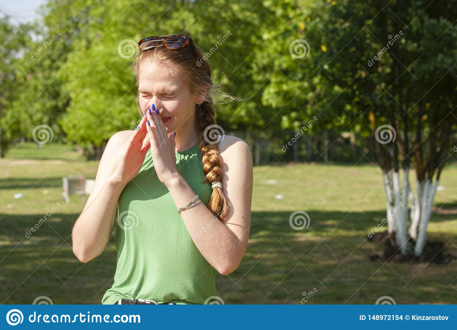 Young woman with allergy during sunny day is wiping her nose