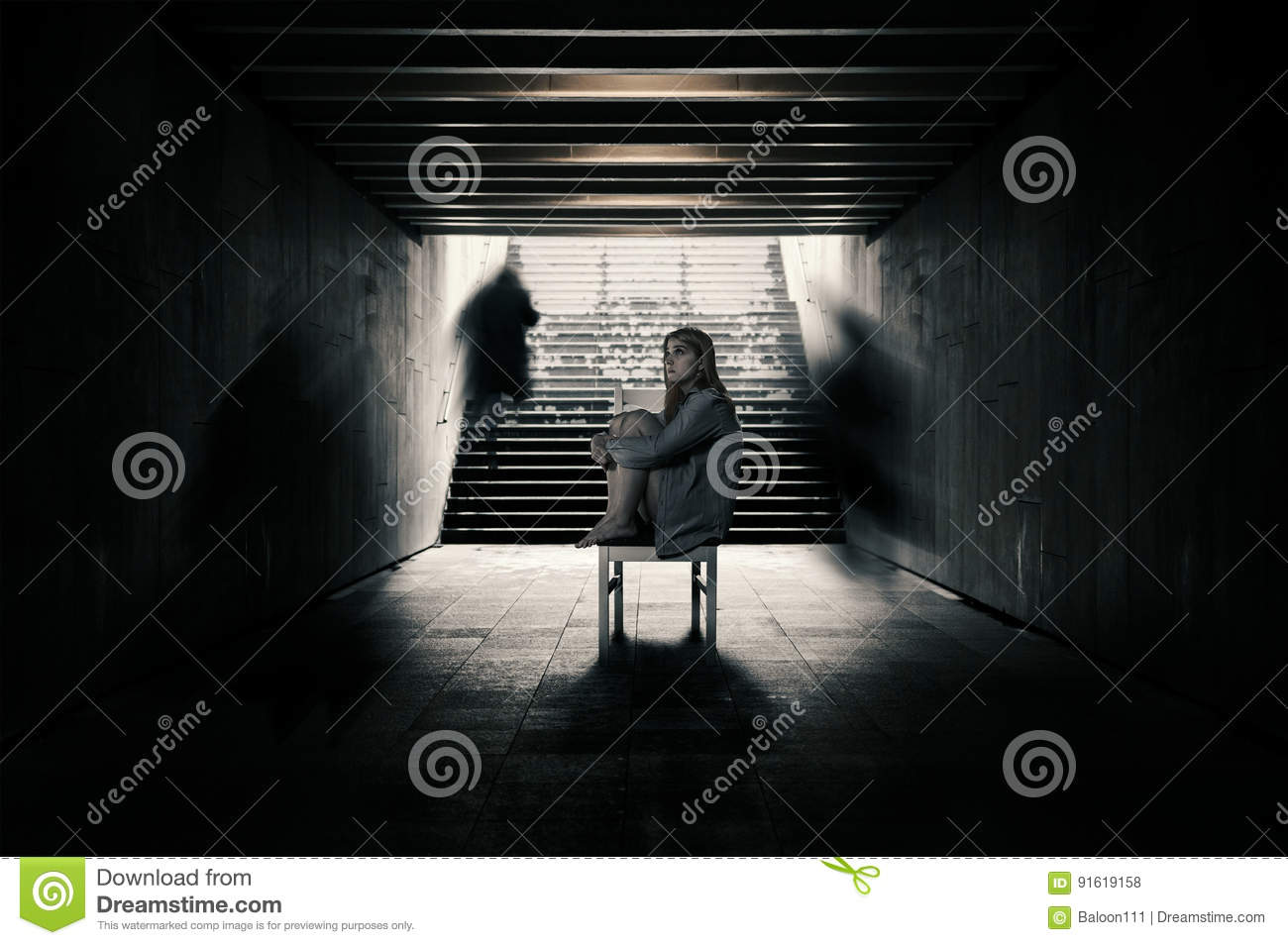 Young woman alone in a tunnel and strangers pass beyond.