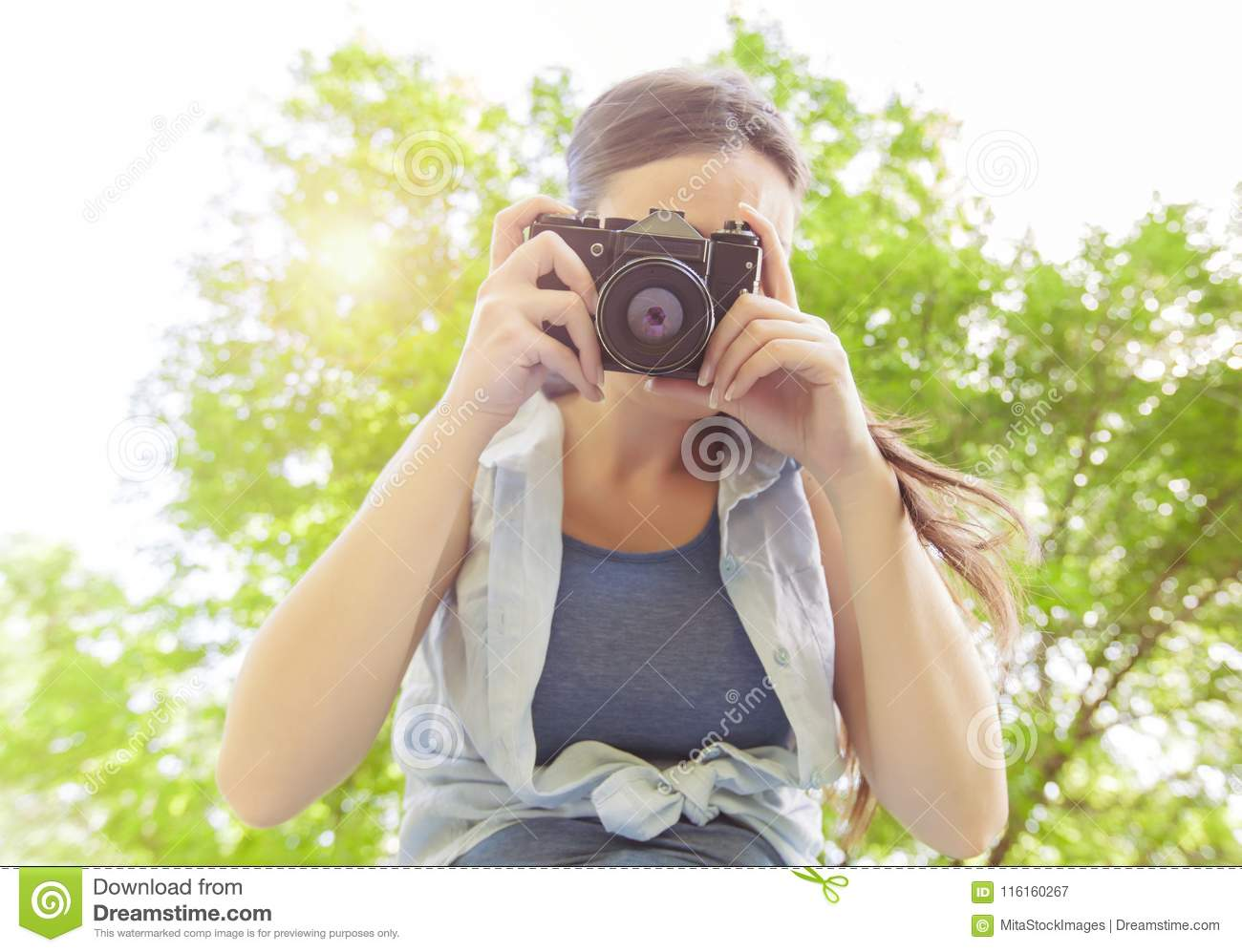 Young woman amateur photographer with vintage camera taking photo in nature