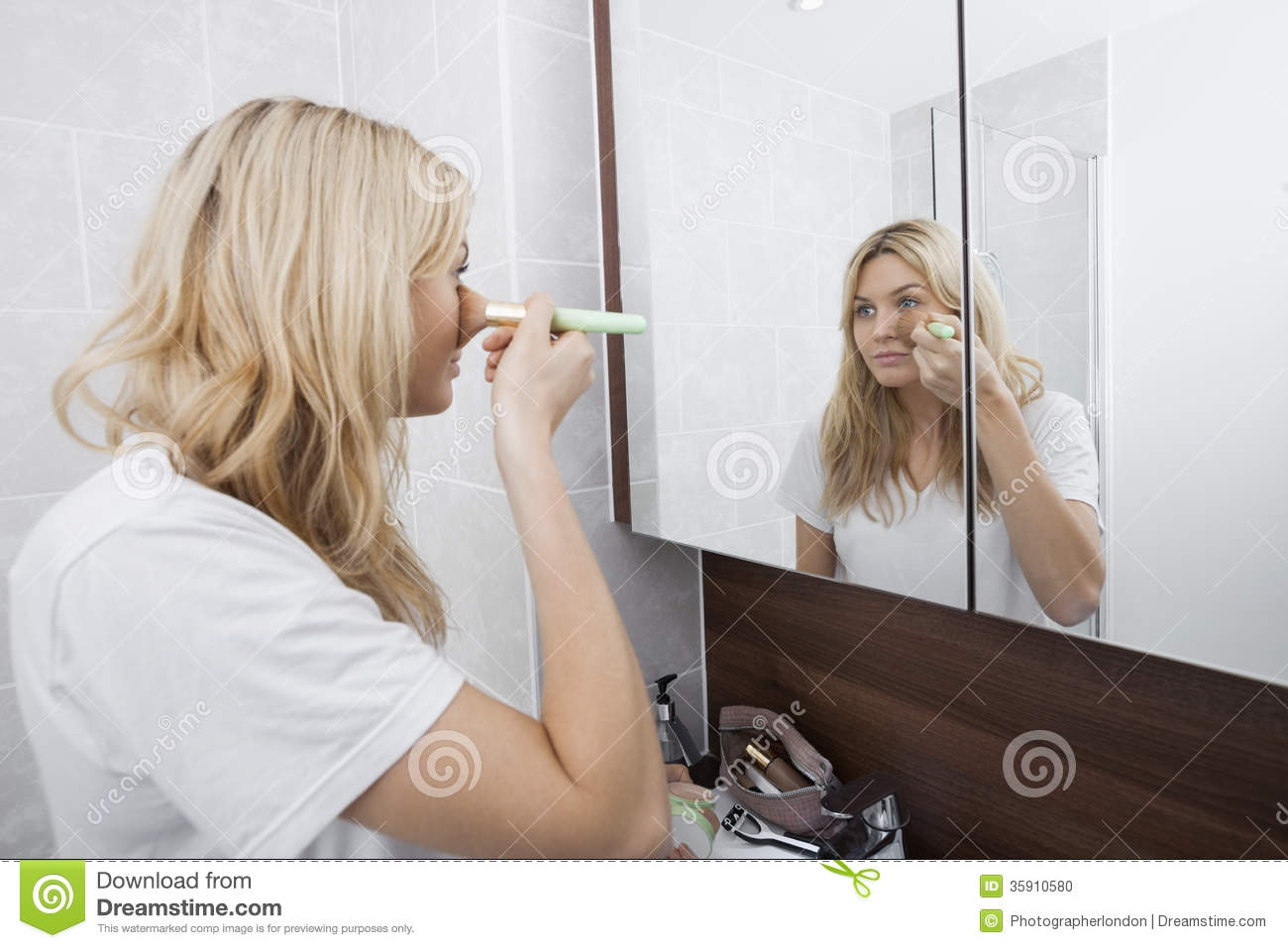 Young woman applying blush while looking at mirror in for Looking mirror