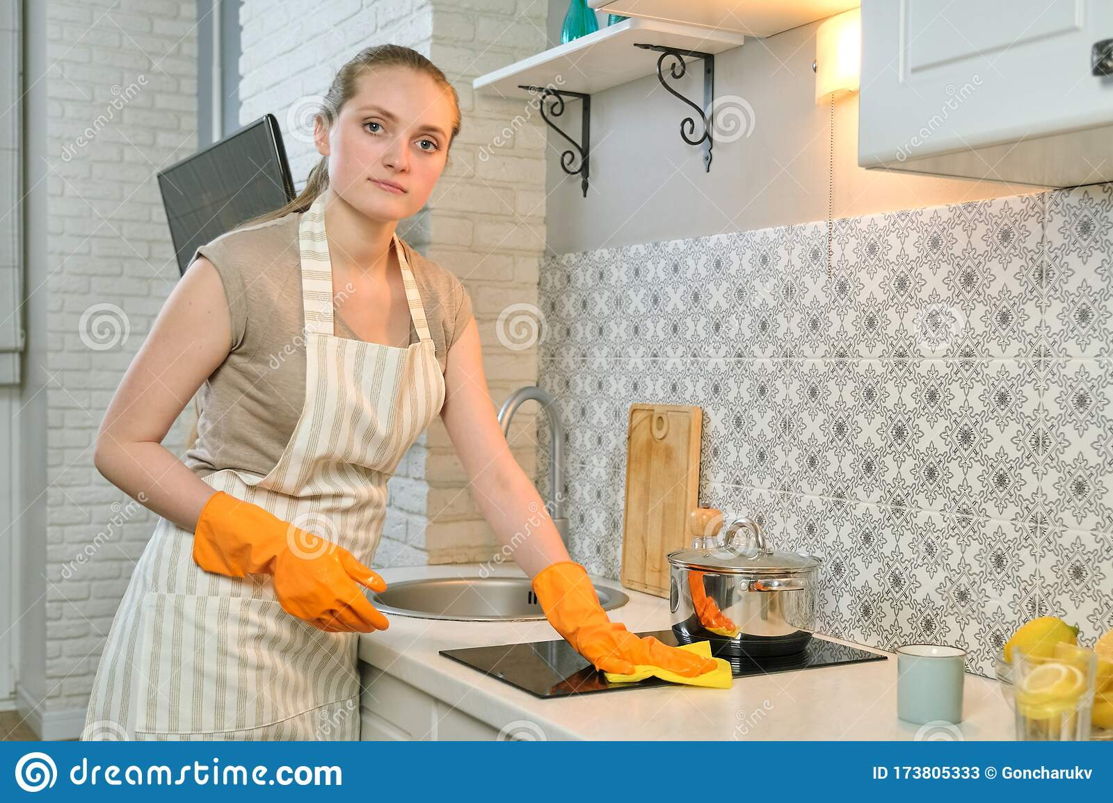 Young Woman In Apron Gloves Cleaning Washing Hob With Rag ...