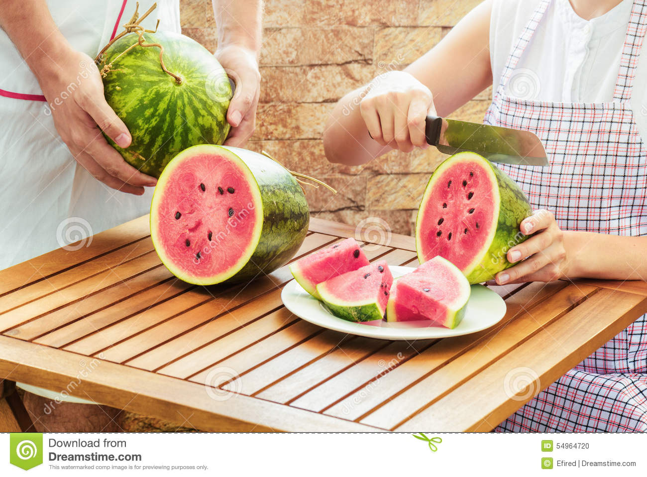 Young woman in apron slicing fresh ripe juicy watermelon