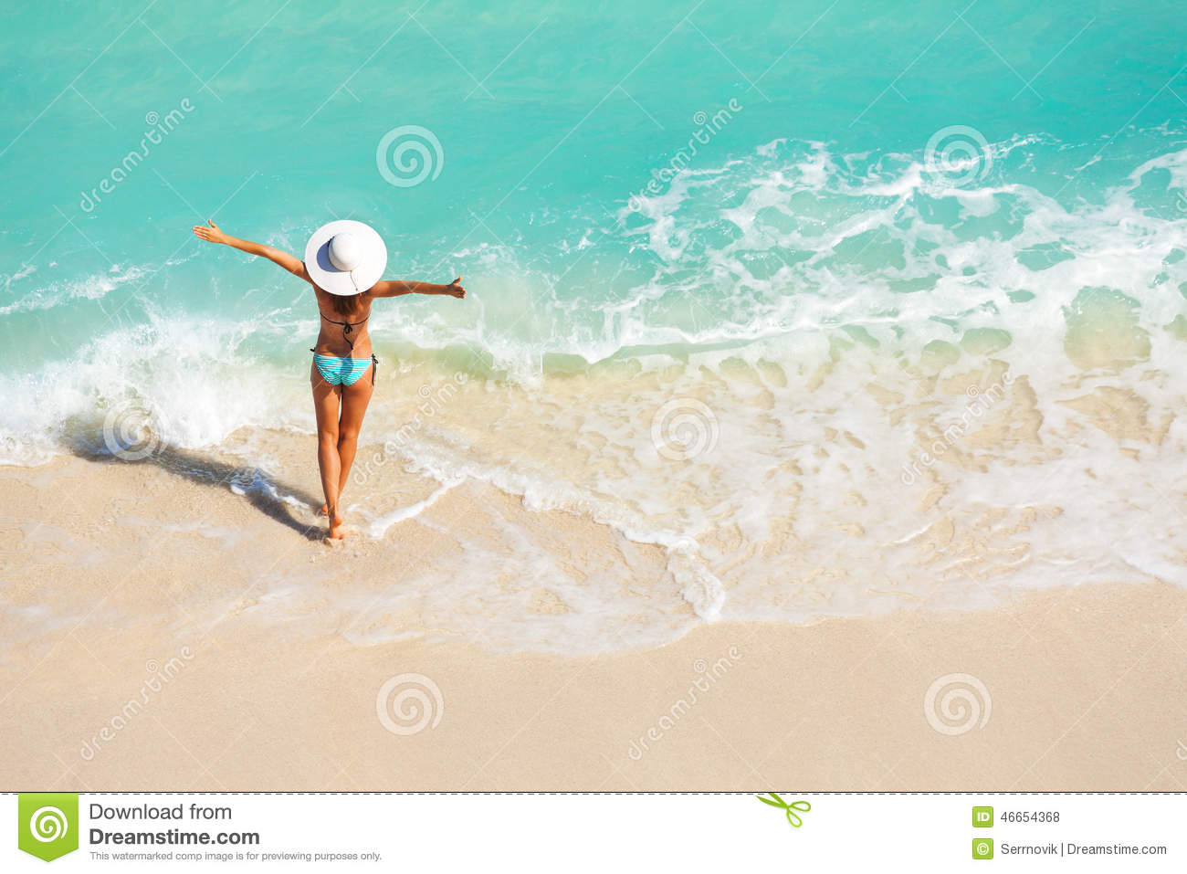 Young girl in a sun hat washing sand off her feet in a