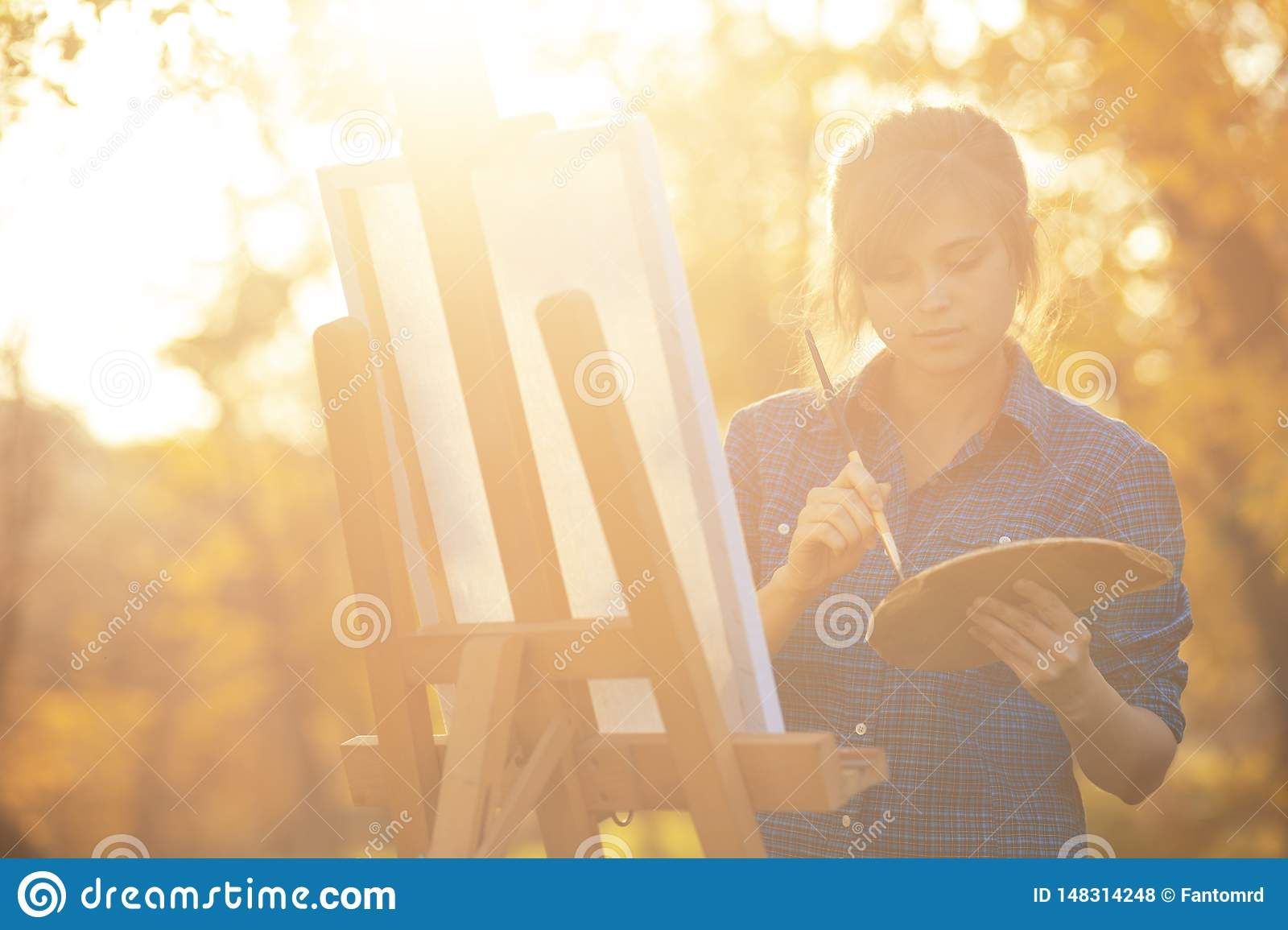 Young woman artist drawing a picture on canvas on an easel in nature, a girl with a brush and a palette of paints working inspired