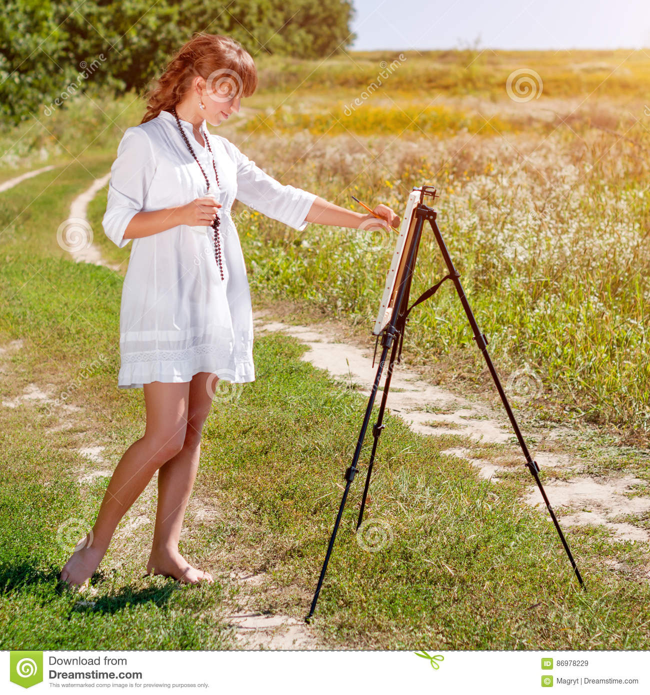 Young Woman Artist At The Easel Painting Landscape