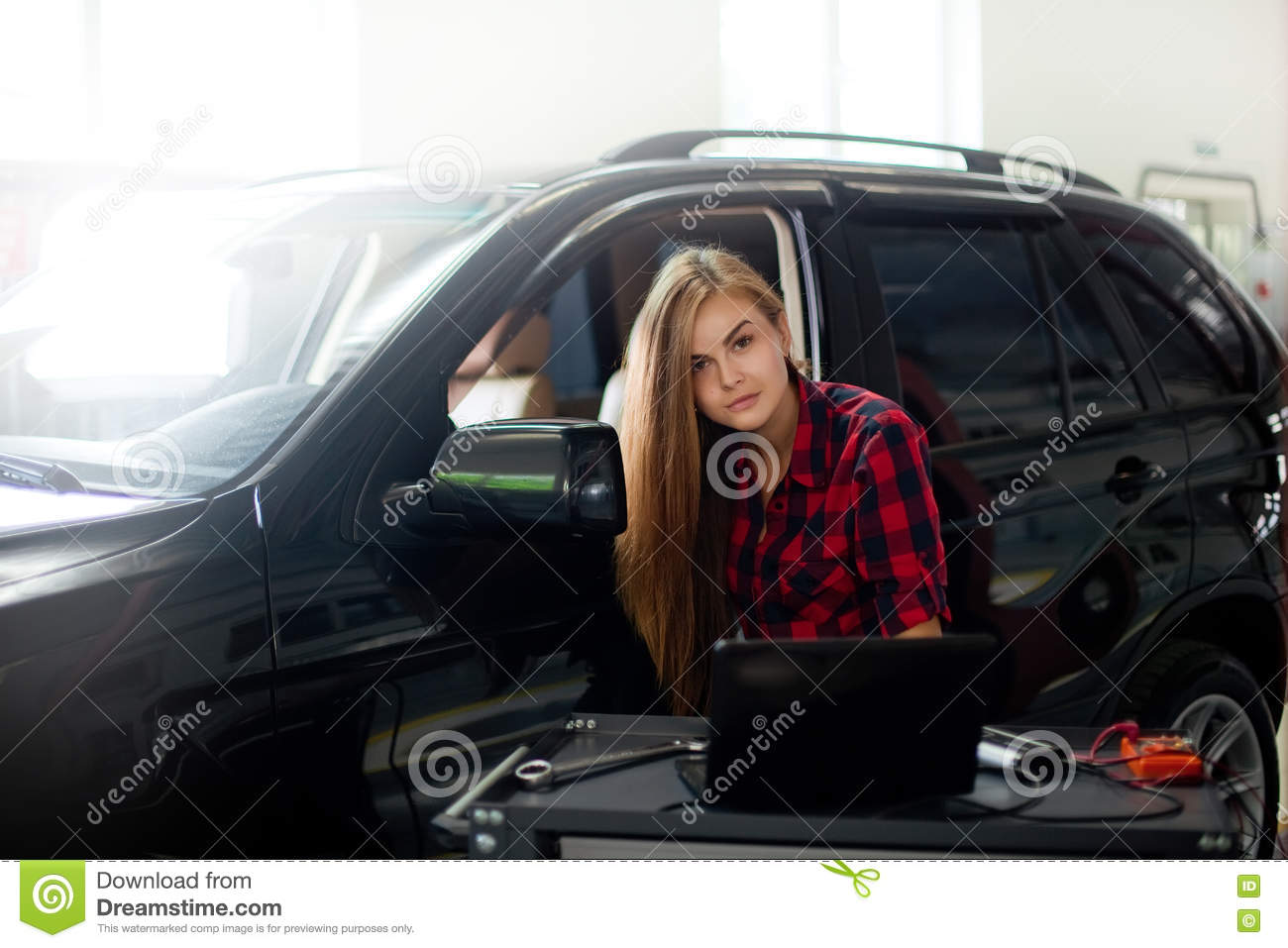 Young woman as a mechanic in checked shirt witch for Garage diag auto
