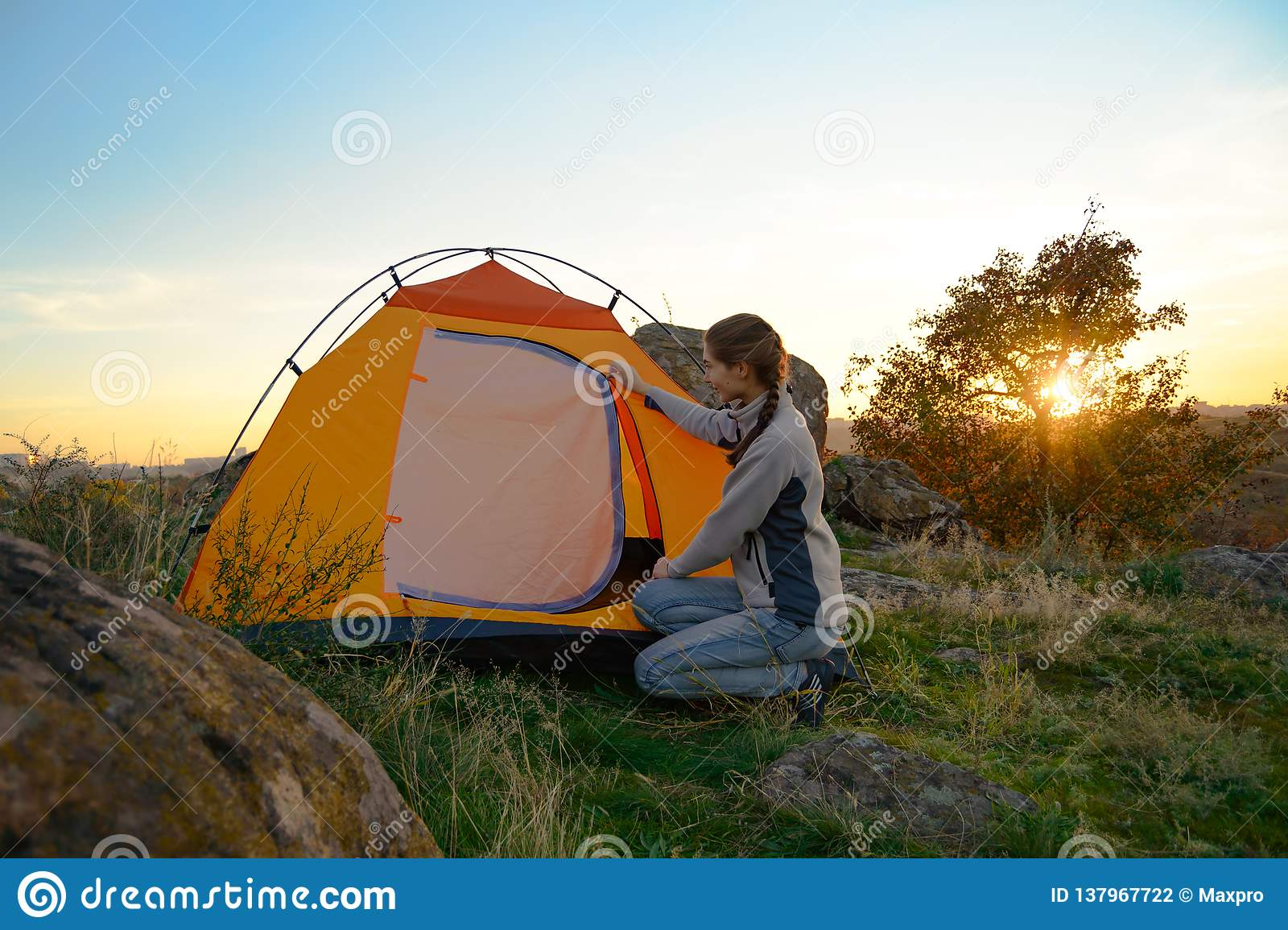 Young Woman Assembling the Tent at Sunset in the Mountains. Adventure and Travel.