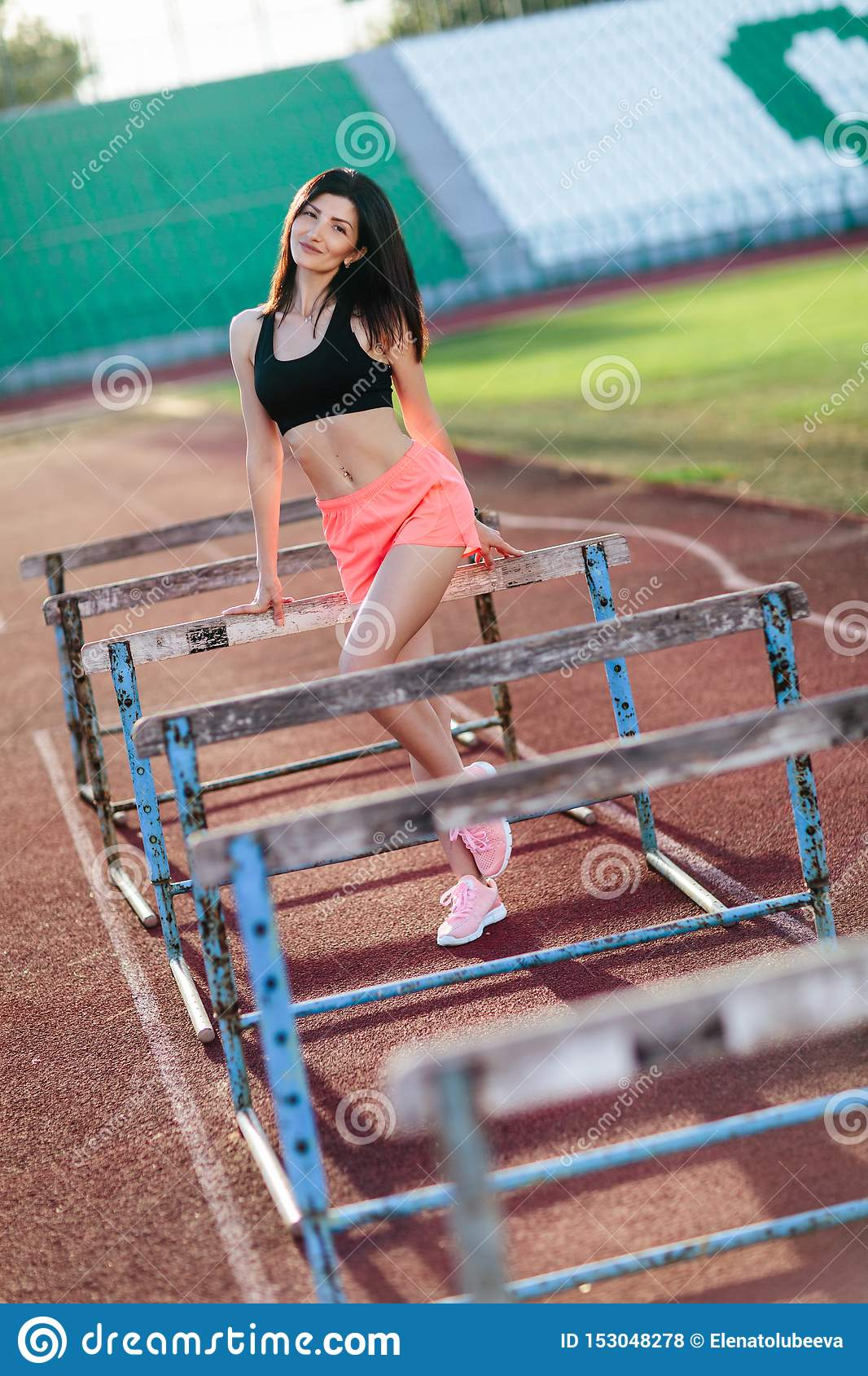 Young brunette woman athlete on stadium sporty lifestyle standing on track posing near the barriers running jumping to camera