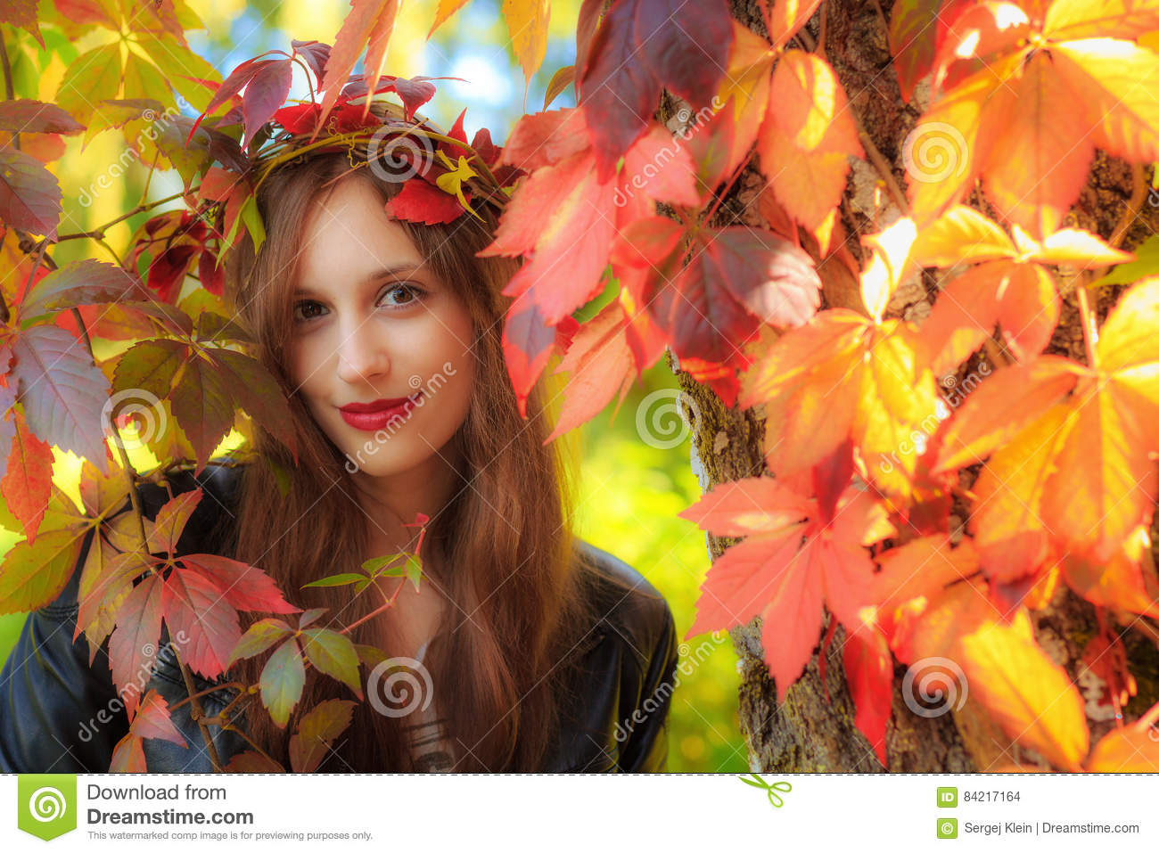 A young woman in an autumn forest with leaves in her hair