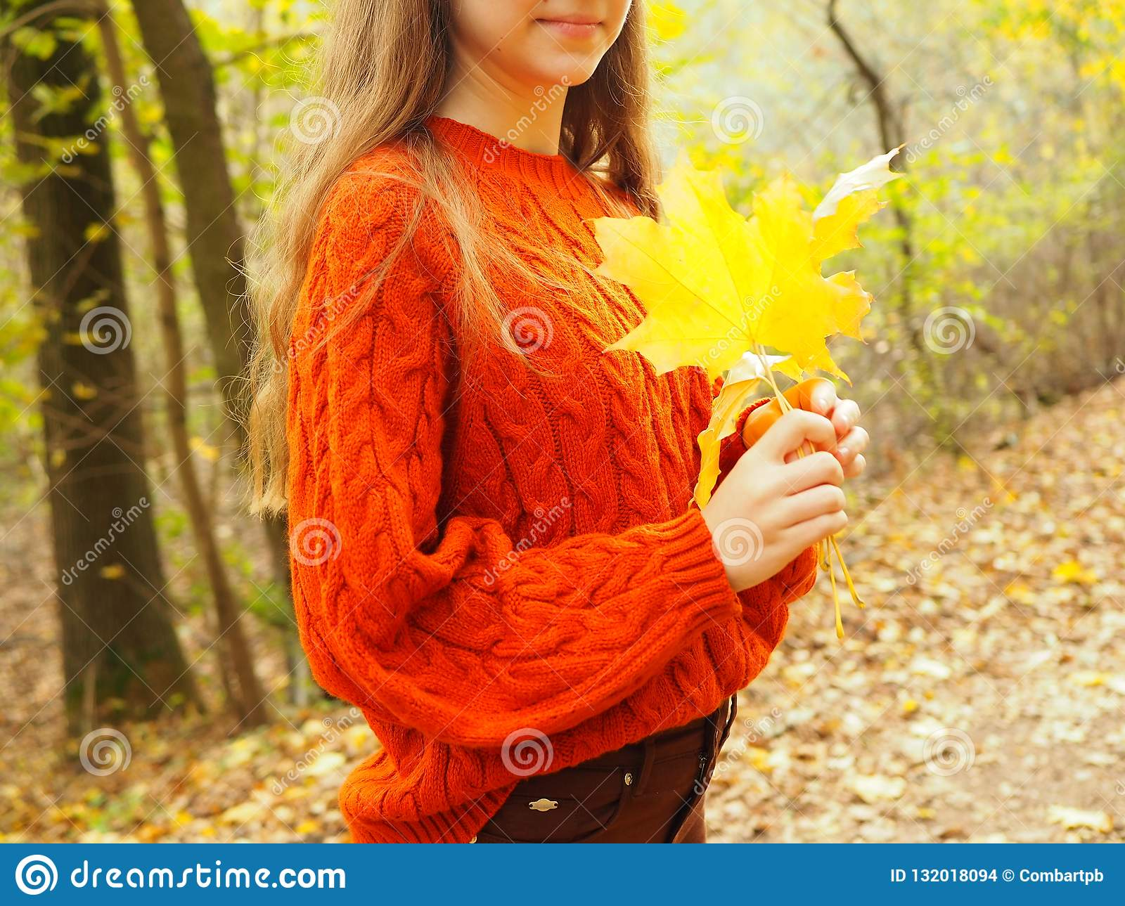 Young woman in autumn park, teenager with yellow leaves