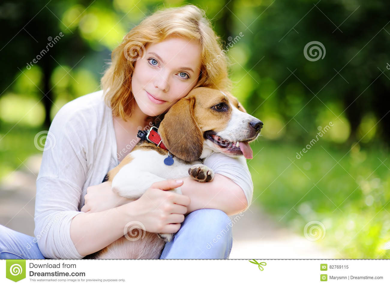 Young woman with Beagle dog in the park